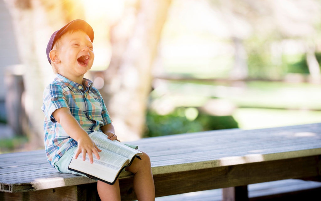 a boy sitting on a bench laughing