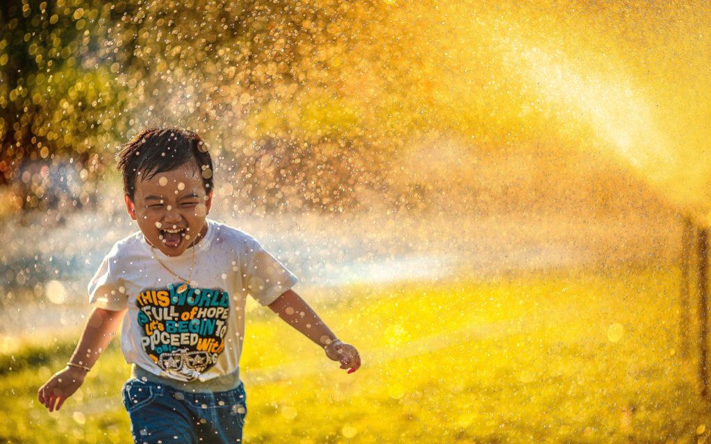 a boy laughing in sprinkles of water